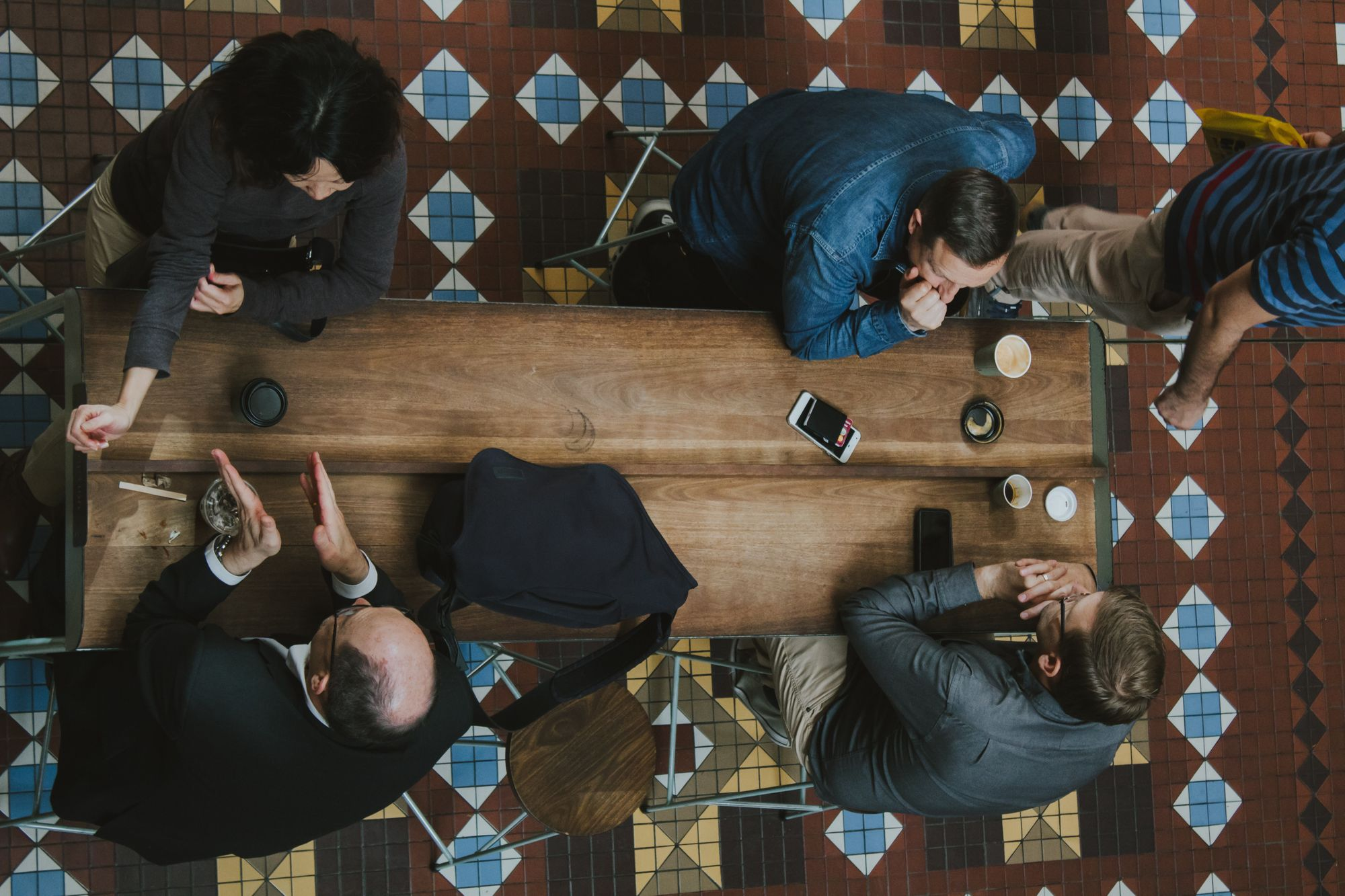 overhead shot of four people talking in coffee shop